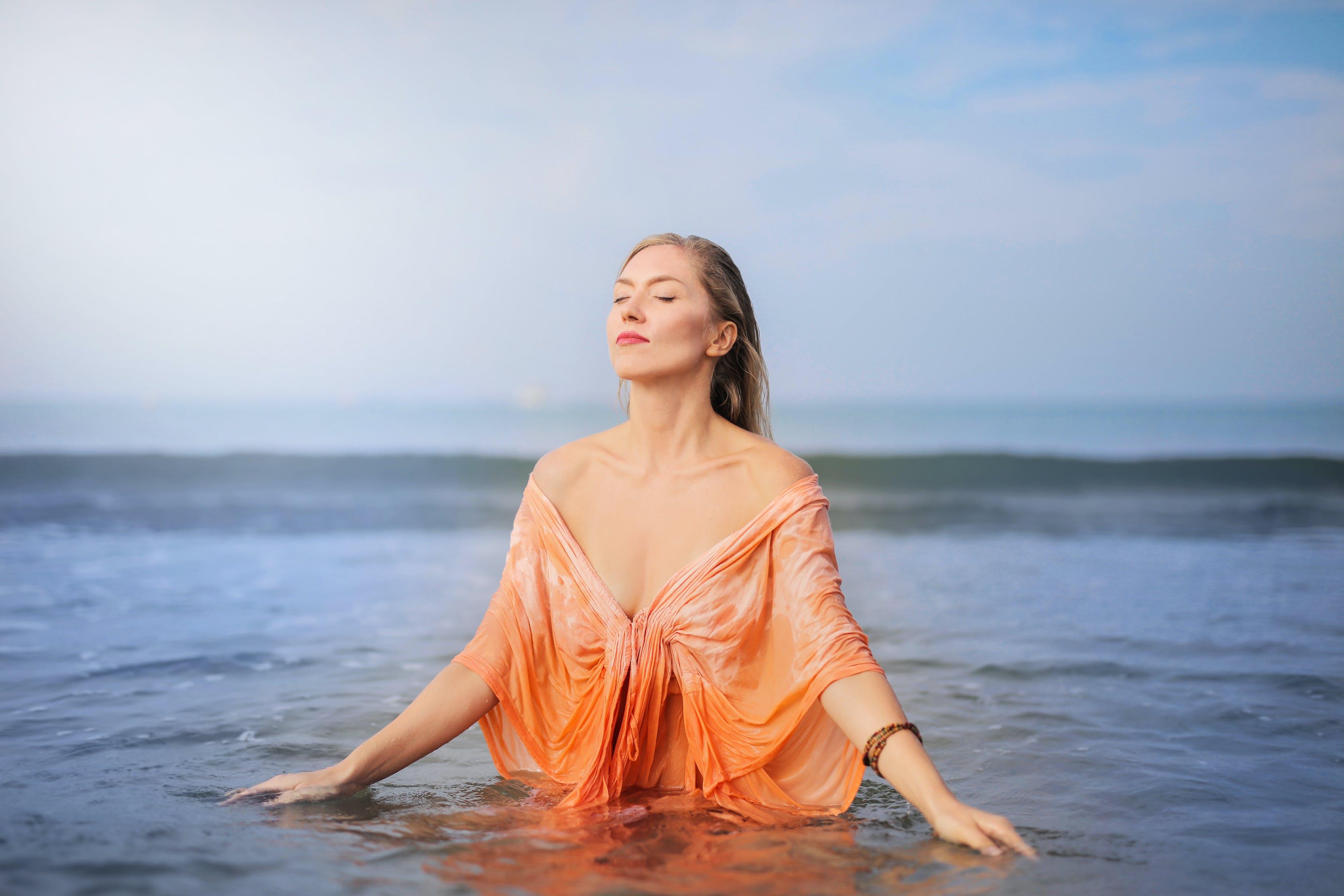Фотография женщины в оранжевой вершине, стоящей в водоеме с закрытыми глазами