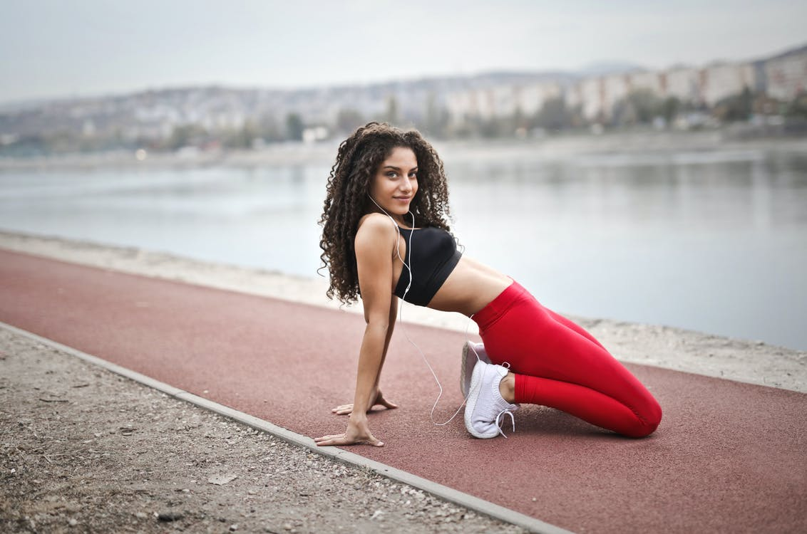 Selective Focus Photo of Woman in Black Sports Bra and Red Leggings Stretching Near Body of Water