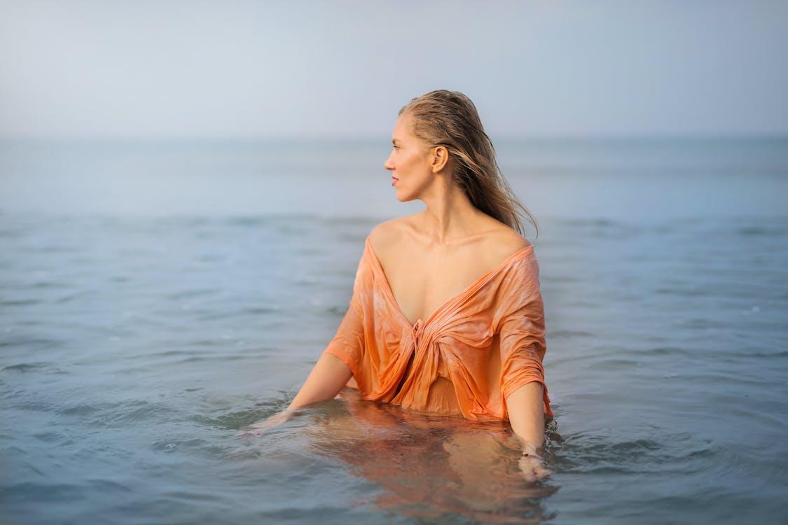 Photo of Woman in Orange Top Standing in Body of Water Looking Away