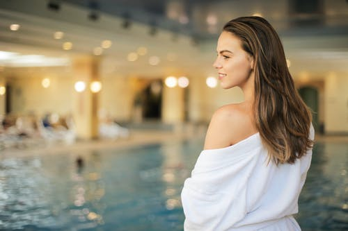 Selective Focus Back View Photo of Smiling Woman in White Robe Standing by Poolside