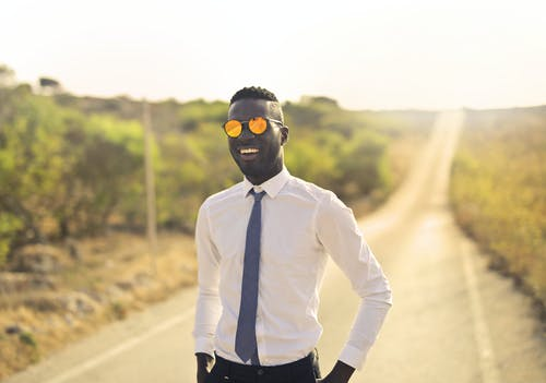 Happy man in formal wear and glasses in countryside