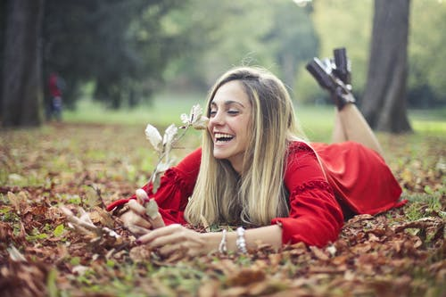 Selective Focus Photo of Laughing Woman in Red Dress Lying on Her Stomach on Dry Leaves While Holding a Dry Branch
