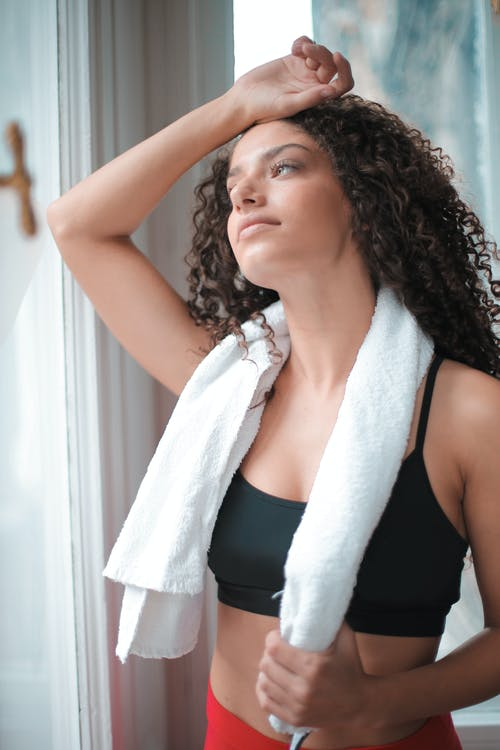 Photo of Woman in Active Wear Holding a Towel Over Her Neck While Standing by a Window