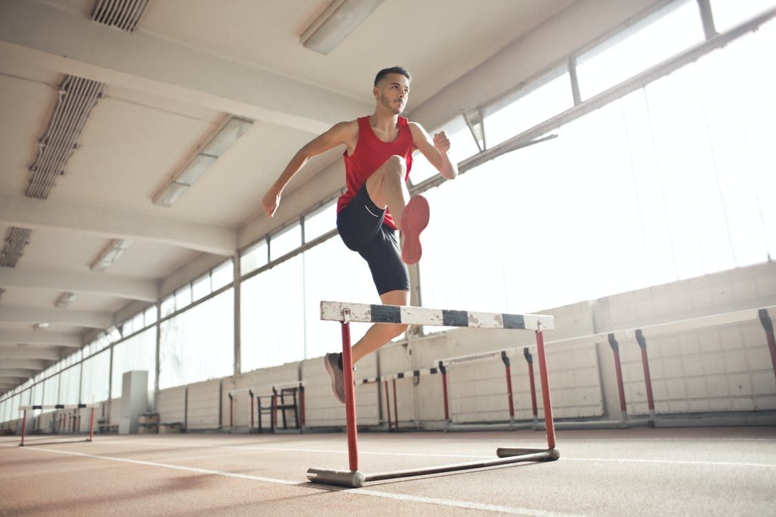 Strong young sportsman jumping over barrier
