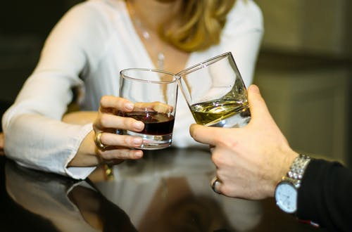 Crop unrecognizable man and woman clinking glasses of alcohol beverages during  romantic date in restaurant