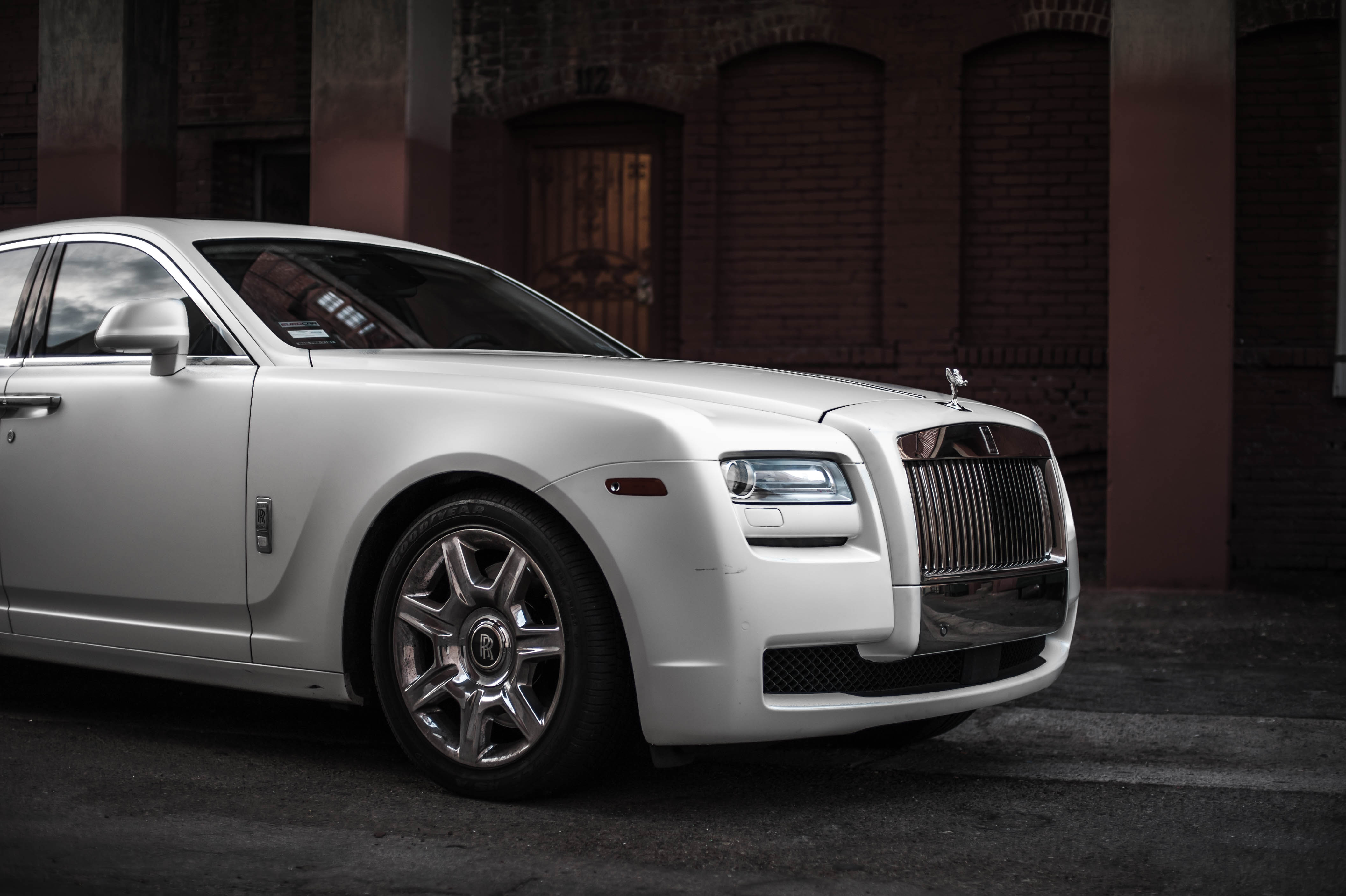 photo of white rolls royce ghost parked near brown building