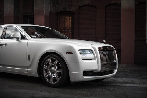 Photo of White Rolls-Royce Ghost Parked Near Brown Building