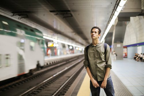 Photo of Man in a Green Shirt Standing Alone on Train Station Platform
