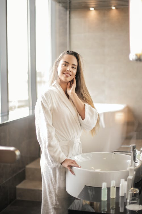Photo of Smiling Woman in White Bathrobe Standing in the Bathroom Next to a Sink