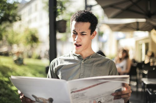 Selective Focus Photo of Surprised Man in Green Button Up Shirt Reading Newspaper