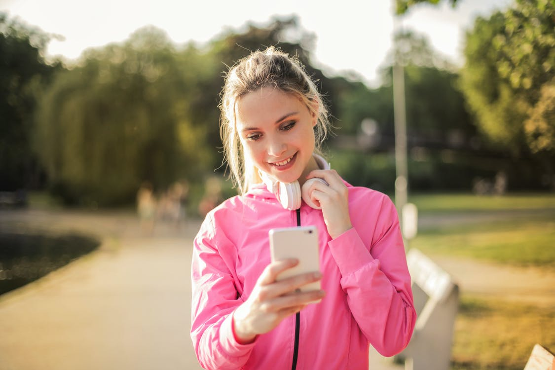 Selective Focus Photo of Smiling Woman in a Pink Jacket with White Headphones on her Neck Using a White Phone