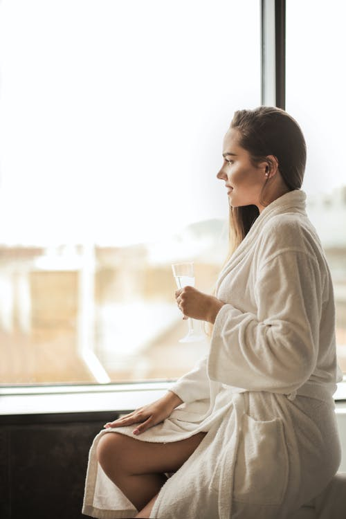 Side View Photo of Woman in White Robe Sitting Next to a Window While Holding a Glass of Champagne