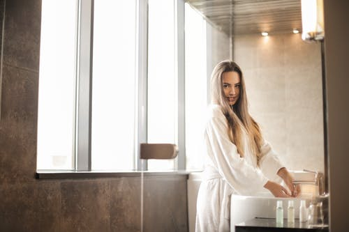 Photo of Woman in White Bathrobe Standing in the Bathroom While Washing Her Hand at a Sink