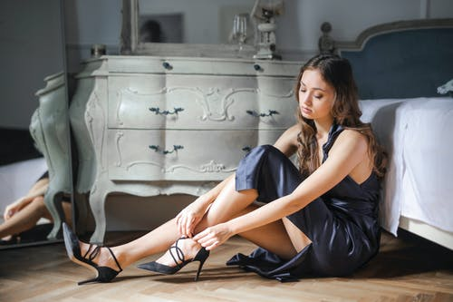 Photo of Woman in a Black Sleeveless Dress Sitting on the Floor While Fastening Her Shoes