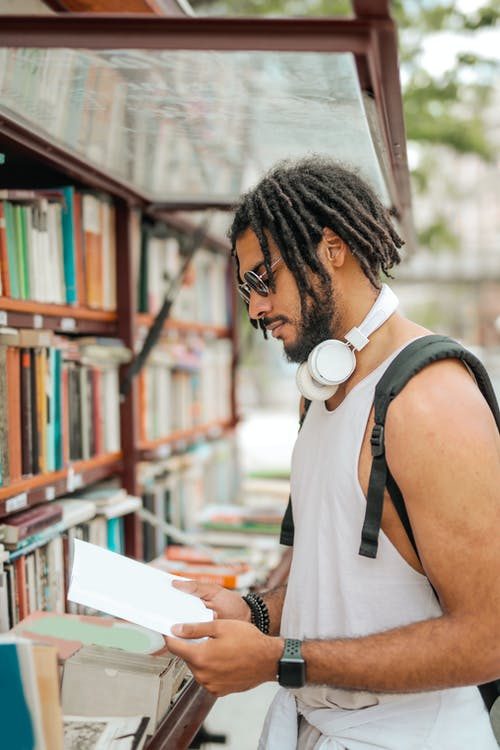 Cool trendy ethnic man with dreadlocks reading book on street