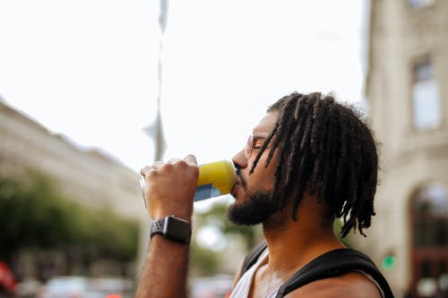 Side view of adult Hispanic guy with dreadlocks in sunglasses and casual clothes with backpack and smart watch drinking yummy beverage from vivid yellow can while standing with eyes closed on street in downtown