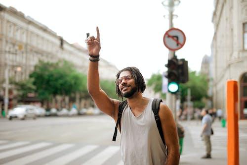 Feliz Hombre étnico Con Mochila Llamando Taxi En La Calle