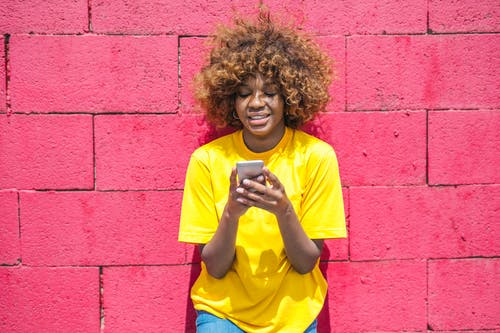 Woman in Yellow Shirt Holding Cellular phone