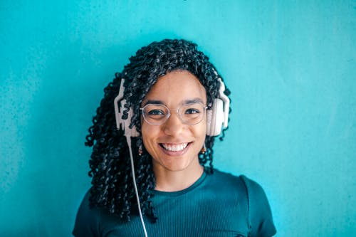 Portrait Photo of Smiling Woman in Black T-shirt ans Glasses Wearing White Headphones