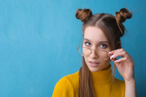 Portrait Photo of Woman in Yellow Turtleneck Sweater and Eyeglasses In Front of Blue Background