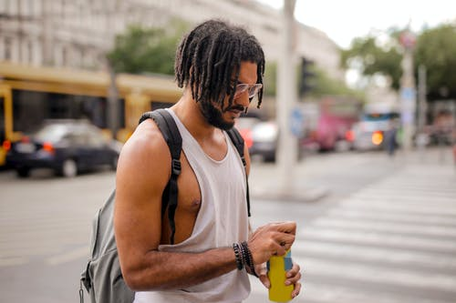 Cool ethnic man with dreadlocks drinking beverage while walking along street in city