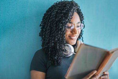 Femme En Chemise Noire Portant Des écouteurs Blancs