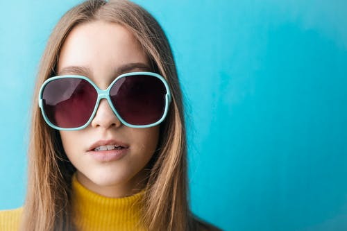 Close-up Photo of Woman in Yellow Turtle Sweater and Blue Framed Sunglasses In Front of Blue Background
