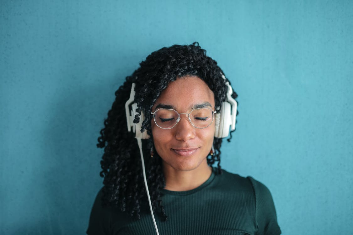 Portrait Photo of Smiling Woman in Black Top and Glasses Wearing White Headphones