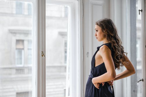 Photo of Woman in Black Dress Standing Beside Glass Window looking Outside