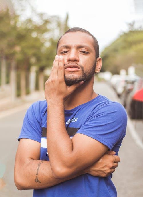 Foto profissional grátis de camiseta azul, de pé, estrada, foco seletivo