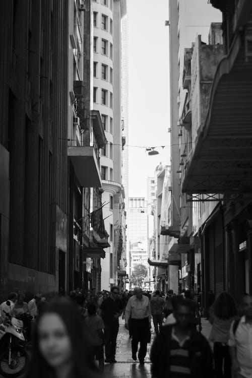Фотография людей, идущих по улице между зданиями в оттенках серого