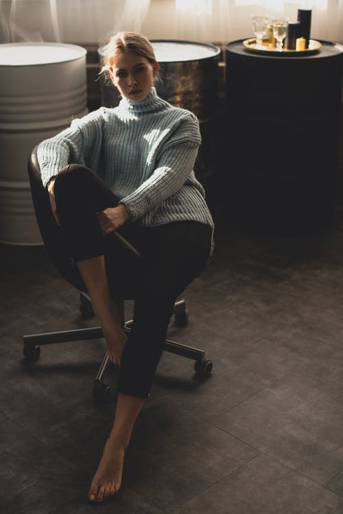 Woman Wearing Blue Sweater and  Black Pants Sitting on Black Office Rolling Chair