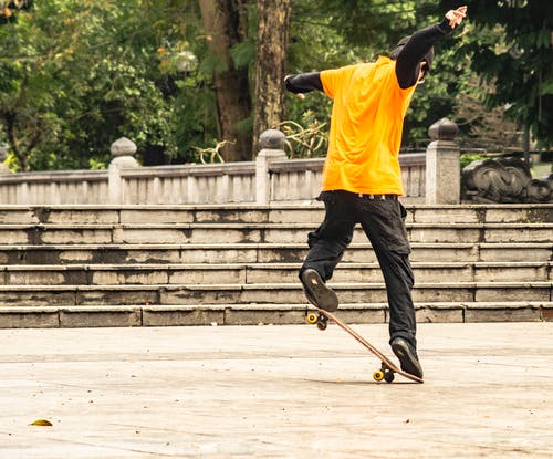Man in Yellow T-shirt and Black Pants Playing Skateboard