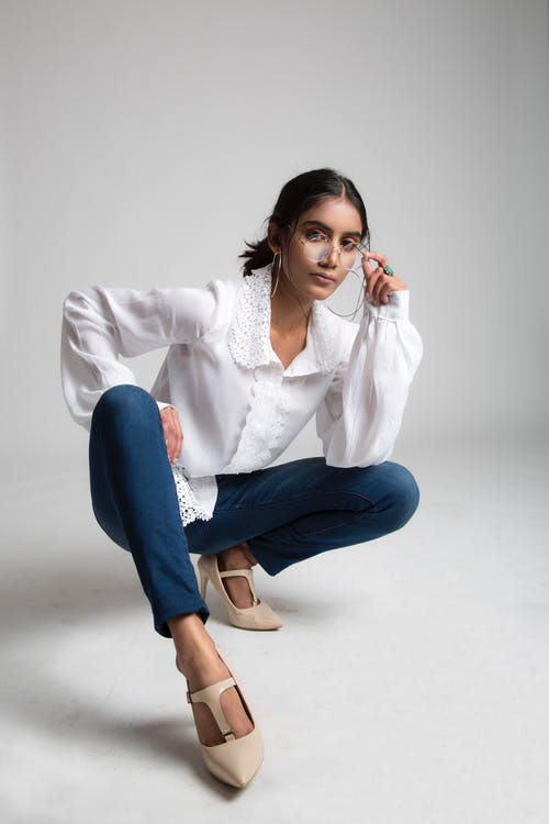 Woman in White Long Sleeve Shirt and Blue Denim Jeans Sitting on White Floor