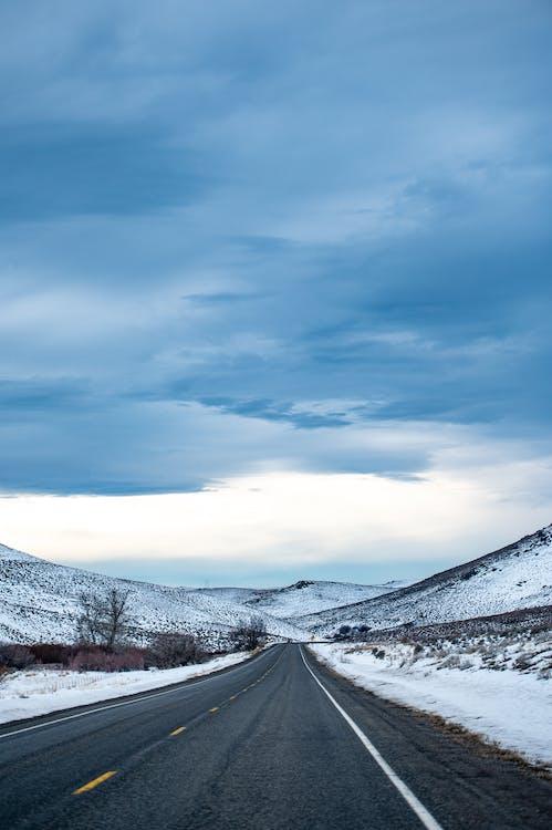 Asphalt Road Between Snow Capped Mountain