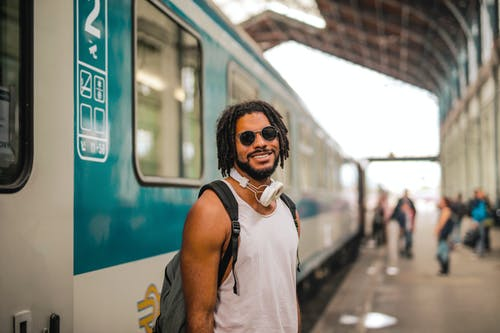Man in White Tank Top Wearing Black Sunglasses Standing Beside Train