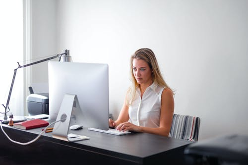 Woman in White Sleeveless Shirt Using Macbook Air on Brown Wooden Table