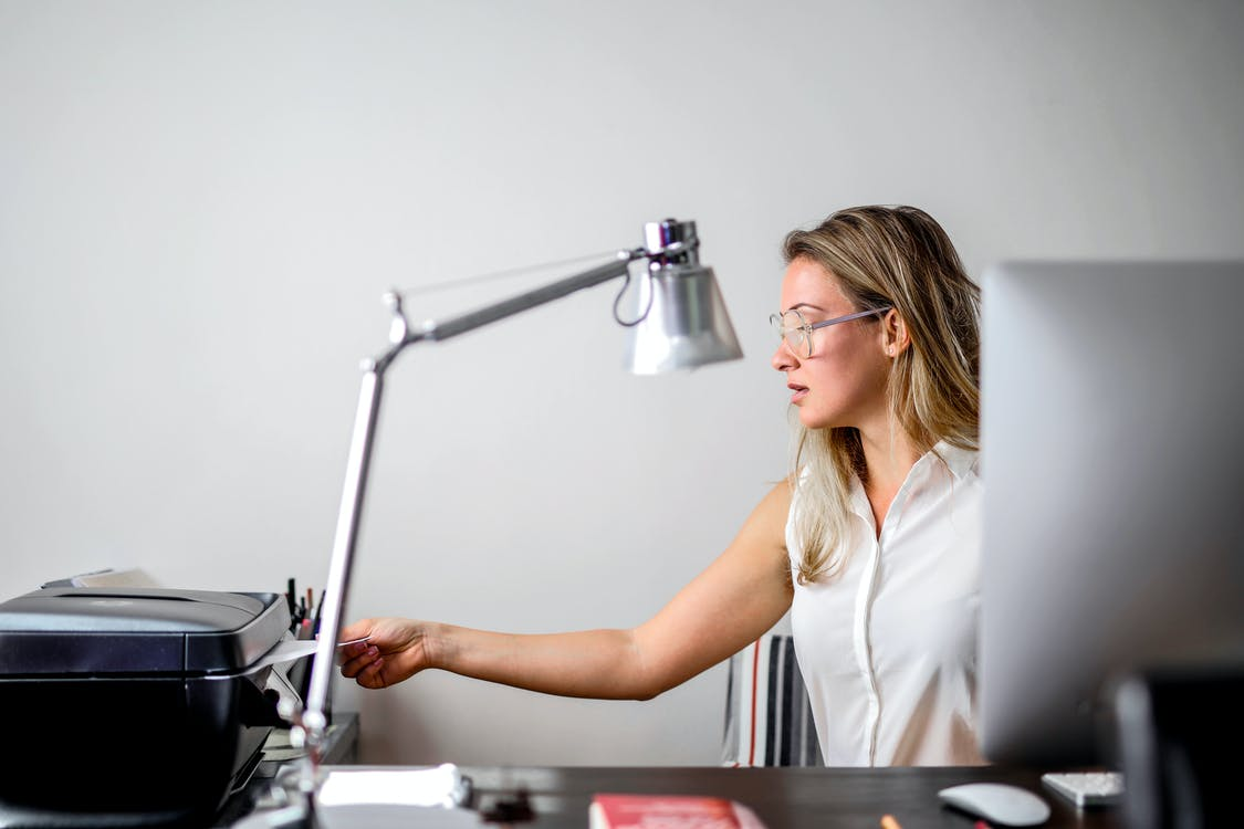 Woman in White Shirt Using a Printer