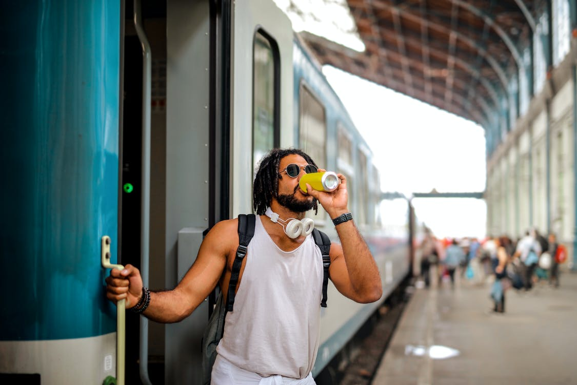 Man Drinking From Can While Standing Near train