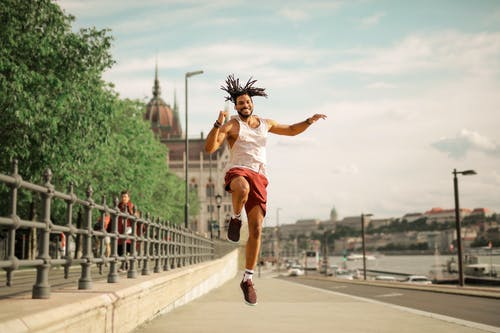 Man Jumping On Concrete Sidewalk