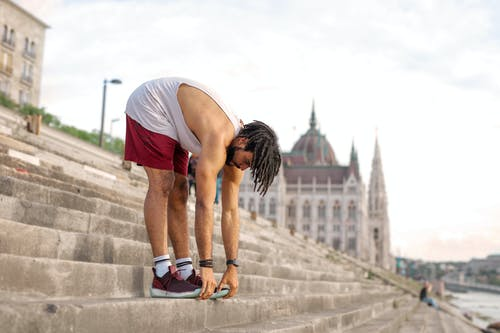 Man in White Tank Top and Red Shorts Stretching on Gray Concrete Stairs