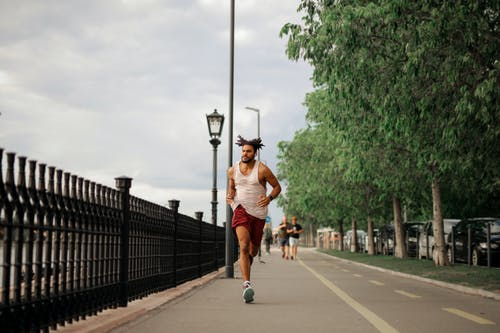 Man in White Tank Top and Red Shorts Running on Road