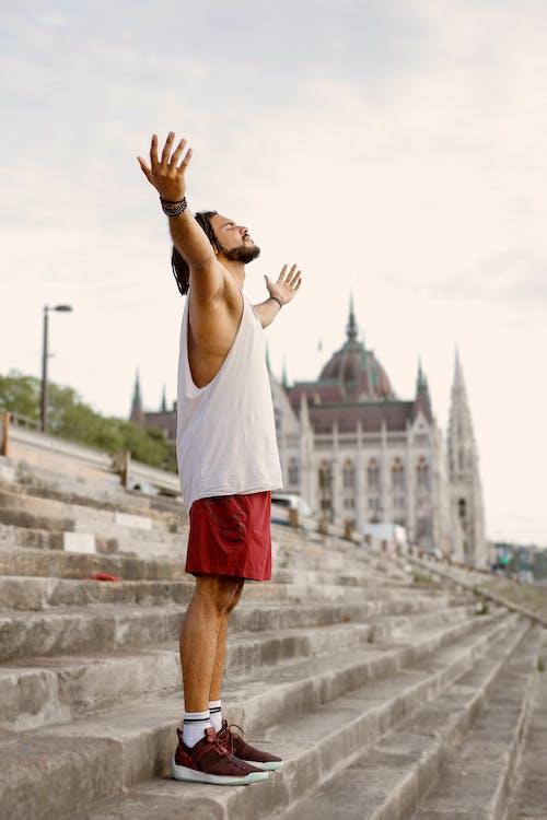 Homem De Camiseta Branca E Short Vermelho Levantando As Mãos