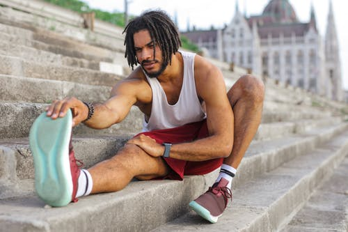 Man in White Tank Top Sitting on Concrete Stairs