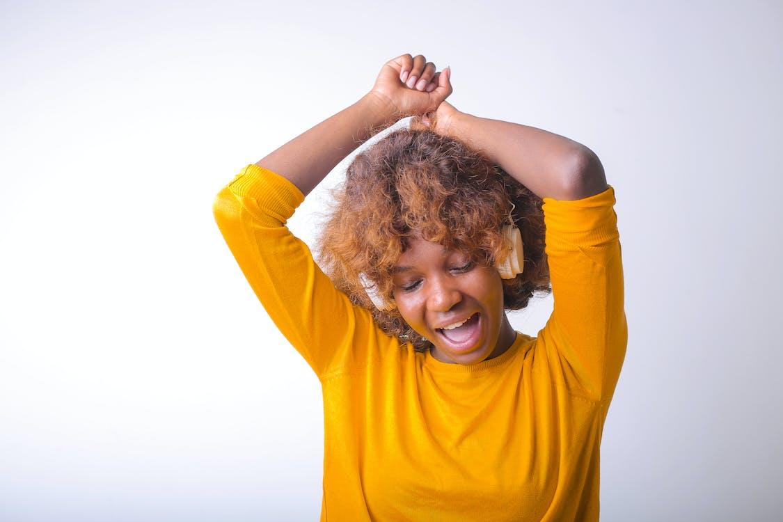 Portrait Photo of Woman in Yellow Top Wearing Headphones