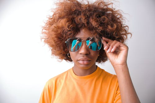 Woman in Orange Crew Neck Shirt Wearing Blue Sunglasses