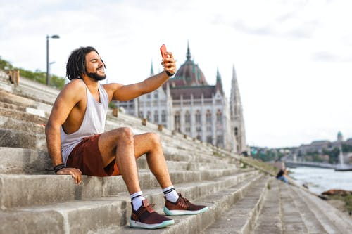 Selective Focus Photo of Smiling Man in White Vest and Red Shorts Taking a Selfie While Sitting on Concrete Stairs