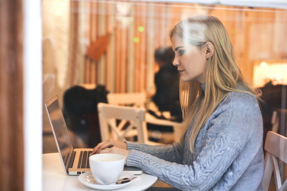 Ernsthafte Junge Frau, Die Netbook Verwendet, Während Heißes Getränk Im Modernen Café Hat