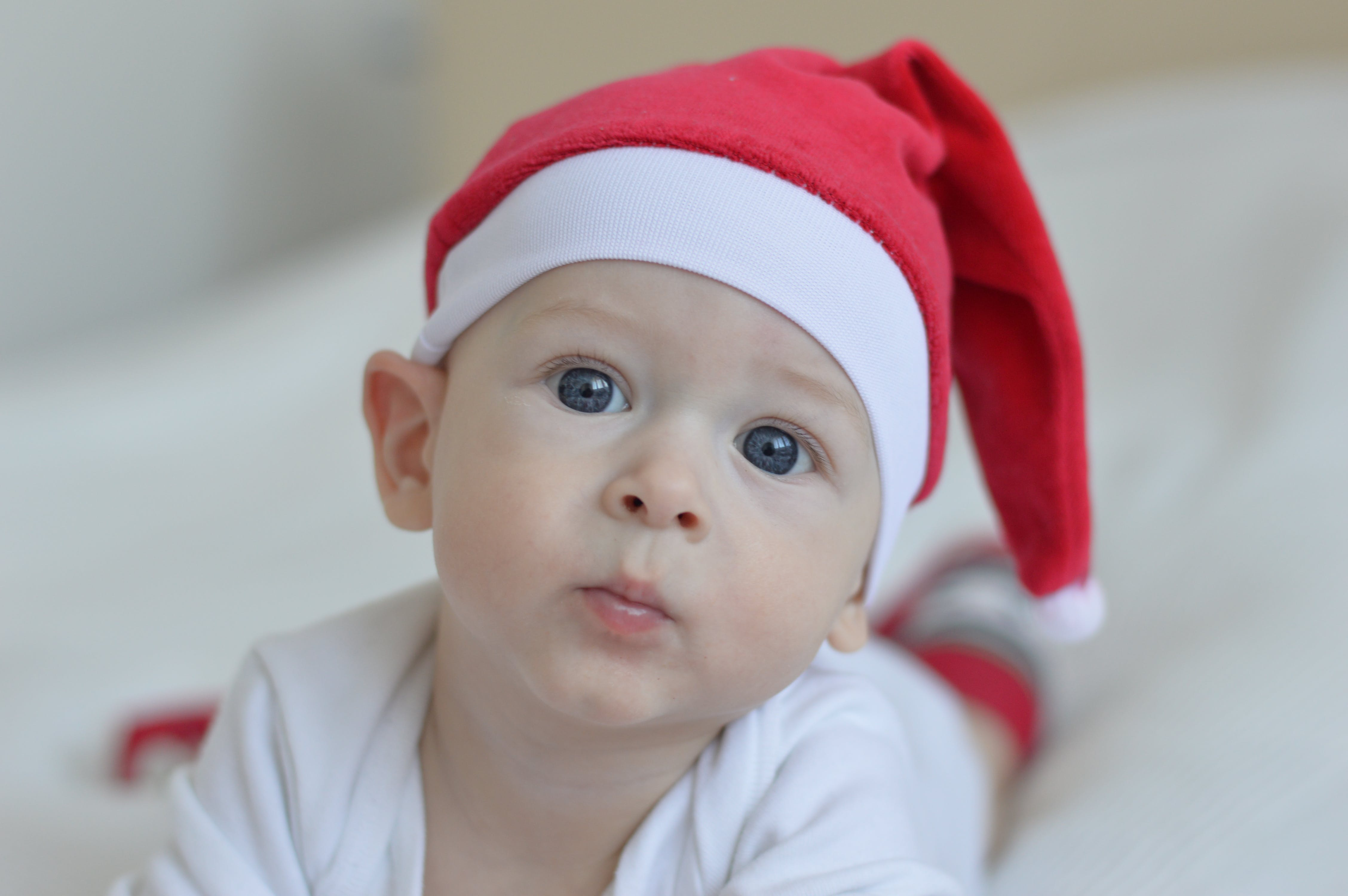 Baby Wearing Red Christmas Hat on White Textile