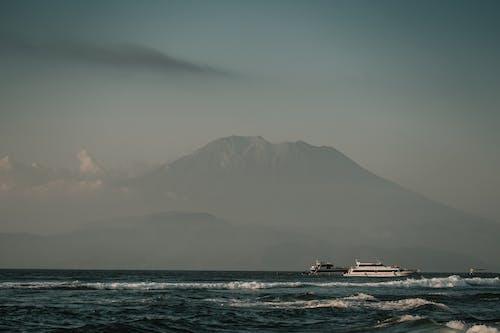 Langit Mendung Di Atas Gunung Dan Laut Dengan Perahu Layar